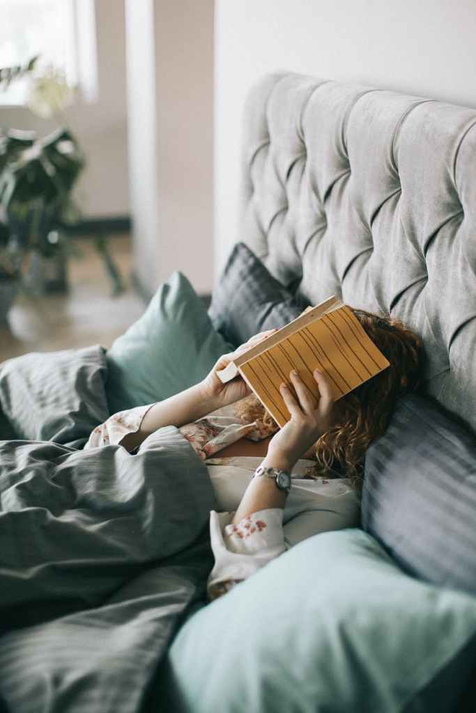 A reader in bed holds a book over their face.